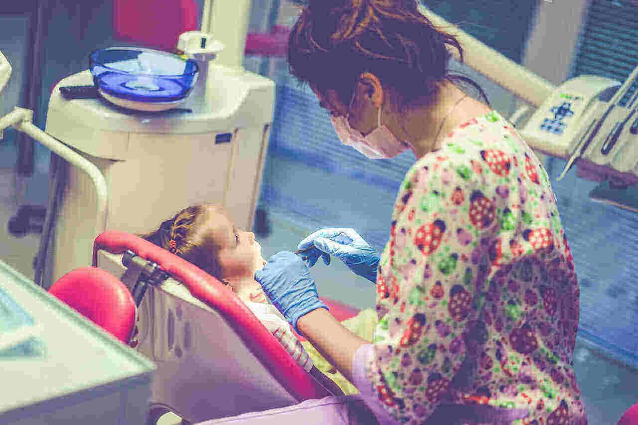 little girl undergoing dental checkup with her dentist