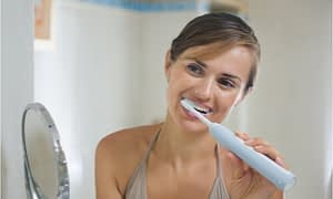 The woman loves to use an electric toothbrush to clean her teeth.